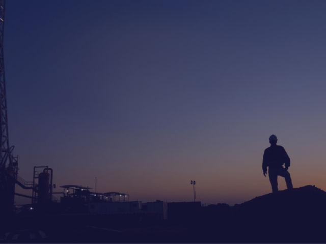 man standing next to a tower at night with the sunset in the background