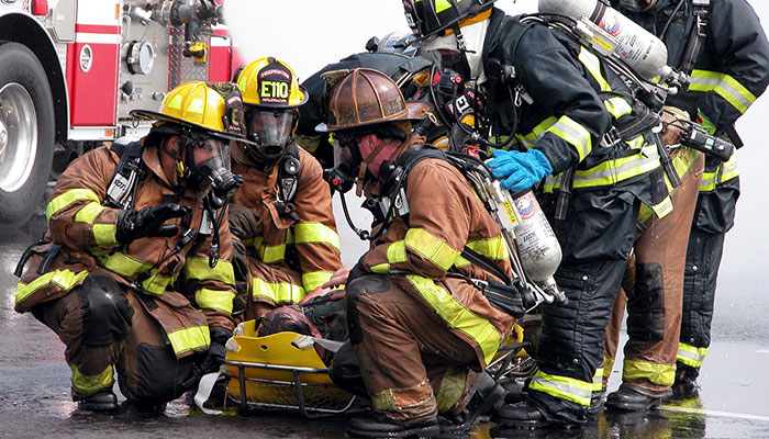 multiple fire fighters kneeling next to a person on a stretcher