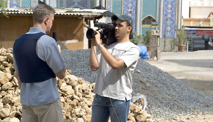 camera man with a white shirt filming a reported speaking