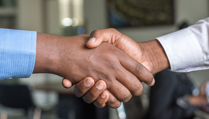 two black men shaking hands wearing blue and white shirts