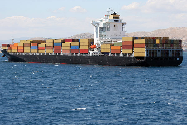 cargo ship in the ocean carrying multi coloured containers