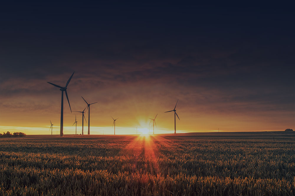 farm land with wind turbines and the sun setting in the background