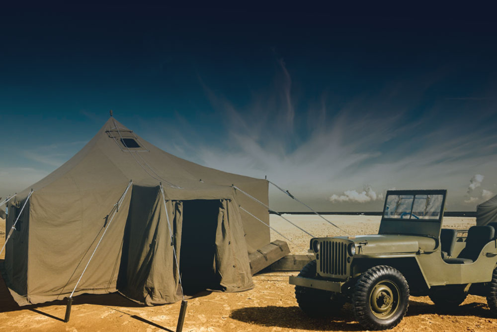 olive green car next to a tent in the desert